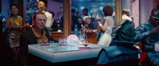 Scotty sits in a bar in Star Trek: Into Darkness. The extras behind him all wear 1960s-inspired fashion.