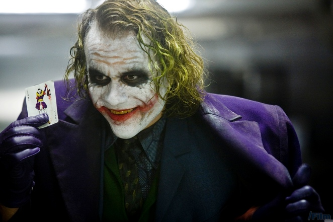 Health Ledger as The joker in Christopher Nolan's The Dark Knight (). The Joker's costume presents a convergence of clown and businessman. His suit is wacky, yet over-priced. Here, he presents a playing card from his inside chest pocket as if it were a business card.