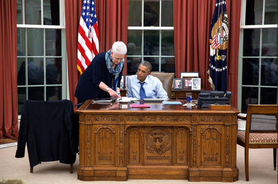 An October 2014 photograph shows Obama occupying 2 seats simultaneously, with his body and his jacket - an extension of his body - so that an aide must stand rather than sit next to him.